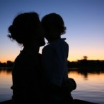 the silhouette of mother with the child against the background of the sunset