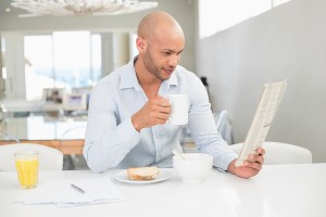 Concentrated young man drinking coffee while reading newspaper a